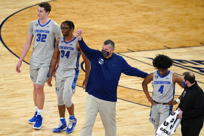 Creighton coach Greg McDermott calls for a player after Shereef Mitchell (4) was hurt, as Ryan Kalkbrenner (32) and Denzel Mahoney (34) walk with them during the second half of an NCAA college basketball game against Connecticut in the semifinals in the Big East men's tournament Friday, March 12, 2021, in New York. (AP Photo/Frank Franklin II)
