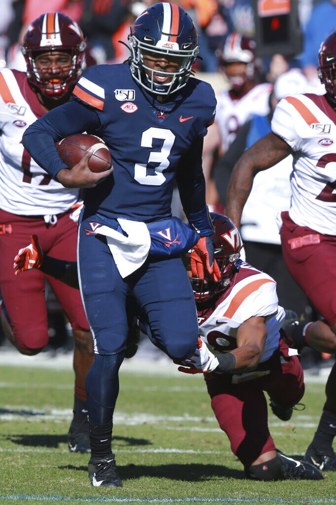 Virginia quarterback Bryce Perkins (3) breaks the tackle of Virginia Tech defensive back Jermaine Waller (28) for a touchdown run during the first half of an NCAA college football game in Charlottesville, Va., Friday, Nov. 29, 2019. (AP Photo/Steve Helber)