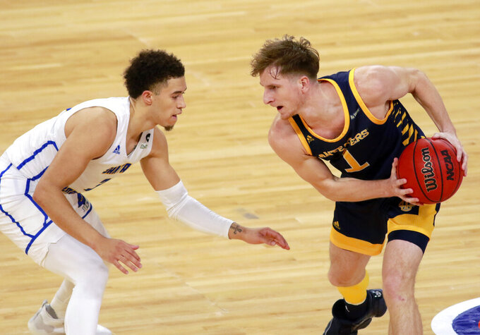 UC Irvine's Dawson Baker keeps the ball from UC Santa Barbara's Jaquori McLaughlin (3) during the first half of an NCAA college basketball game for the championship of the Big West Conference men's tournament Saturday, March 13, 2021, in Las Vegas. (AP Photo/Ronda Churchill)