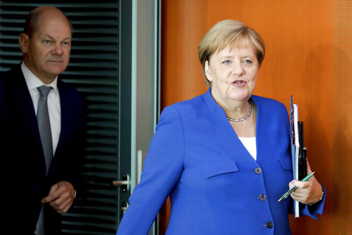 German Chancellor Angela Merkel, right, and German Finance Minister Olaf Scholz, left, arrive for the weekly cabinet meeting at the Chancellery in Berlin, Germany, Wednesday, Sept. 18, 2019. (AP Photo/Michael Sohn)