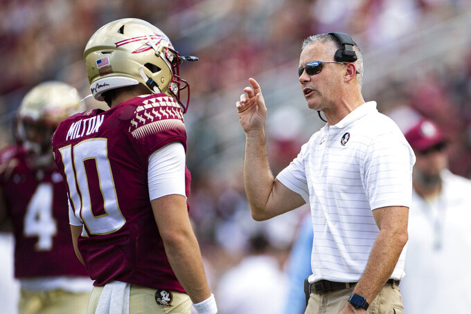 Florida State head coach Mike Norvell talks with quarterback McKenzie Milton in the first half of an NCAA college football game against Louisville in Tallahassee, Fla., Saturday, Sept. 25, 2021. (AP Photo/Mark Wallheiser)