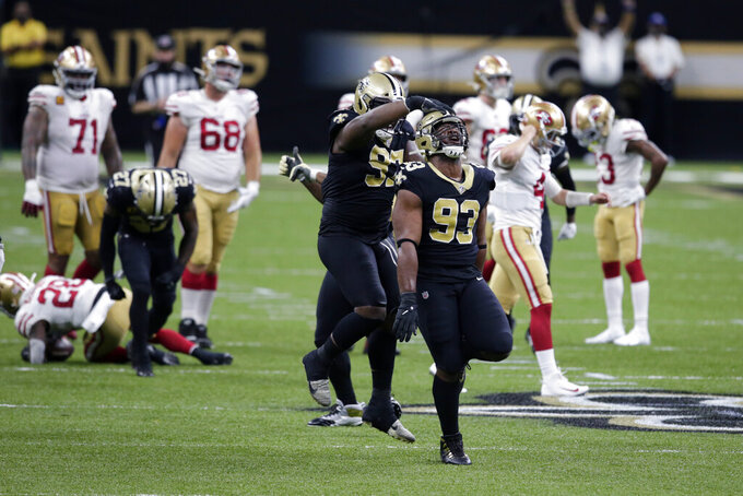 New Orleans Saints defensive tackle David Onyemata (93) and defensive tackle Malcolm Roach (97) celebrated a defensive stop on fourth down in the first half of an NFL football game against the San Francisco 49ers in New Orleans, Sunday, Nov. 15, 2020. (AP Photo/Butch Dill)