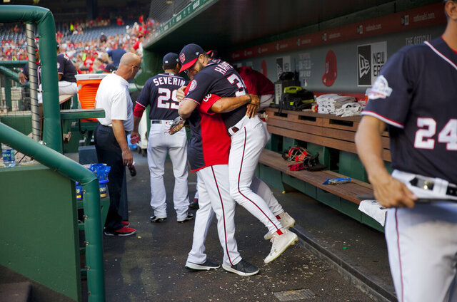 In this May 4, 2018, photo, Washington Nationals Bryce Harper is hugged and lifted off the ground by his manager Dave Martinez in the dugout prior to the start of a baseball game against the Philadelphia Phillies at Nationals Park in Washington. High fives and fist bumps are out. Hugs are a no-go. And just like crying, there's no spitting in baseball, at least for now. Things sure will be different when it's time to play ball in two weeks. (AP Photo/Pablo Martinez Monsivais, File)