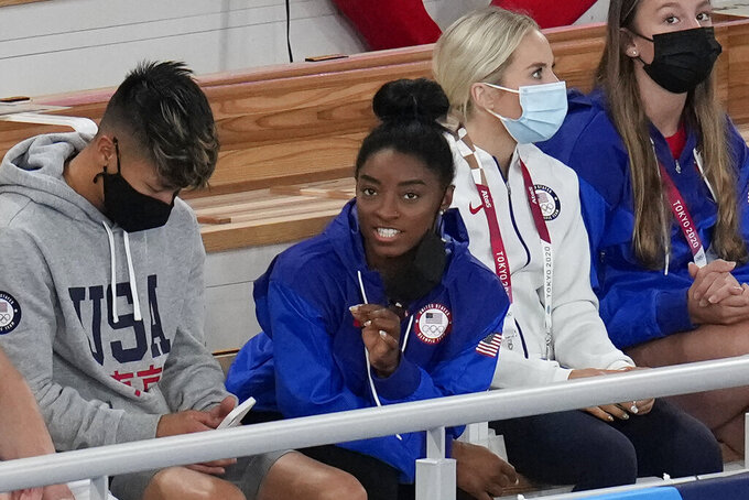 Simone Biles, of the United States, sits at the stands with teammates during the artistic gymnastics men's apparatus final at the 2020 Summer Olympics, Monday, Aug. 2, 2021, in Tokyo, Japan. (AP Photo/Gregory Bull)