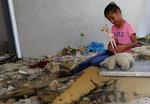 Rahaf Abu Fares, 10, who lost four family members when an Israeli artillery bombardment hit his family house during the 11-day war between Israel and Gaza's Hamas rulers in May, plays with a toy amid the rubble of his house, at the Bedouin village of Umm Al-Nasr, outside the town of Beit Lahia, northern Gaza Strip, Wednesday, Aug. 4, 2021. After initially finding no grounds for disciplinary action, the Israeli military says it is investigating the artillery bombardment that killed six Palestinians, including an infant, in the Gaza Strip last May. (AP Photo/Adel Hana)