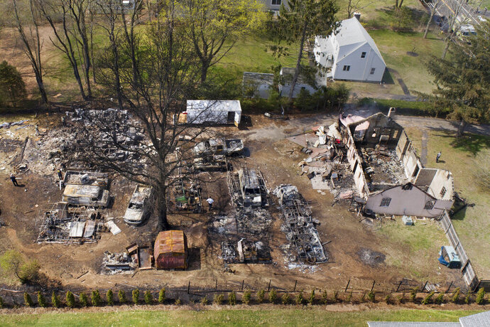 FILE - In this May 3, 2018 file photo, emergency personnel work at the scene of an explosion in North Haven, Conn. Newly released reports are shedding more light on an explosion during a police standoff in Connecticut last year that killed a man and injured nine officers. John Sayre Sr. was killed in the blast in a barn behind his home. (John Woike/Hartford Courant via AP, File)
