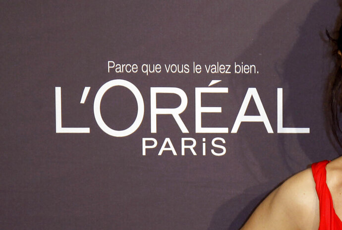 """FILE - In this file photo dated Wednesday, May 23, 2012, the L'Oreal logo at the 65th international film festival, in Cannes, southern France. In a statement issued Saturday June 27, 2020, French cosmetics giant L'Oreal says it will remove words like """"whitening"""" from its skin care products following criticism of the company amid global protests against racism. (AP Photo/Francois Mori, FILE)"""
