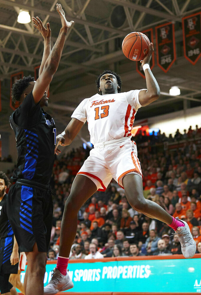 Bowling Green forward Jeffrey Uju (13) shoots against Buffalo forward Montell McRae (1) in the second half of an NCAA college basketball game in Bowling Green, Ohio, Friday, Feb. 1, 2019. (AP Photo/Rick Osentoski)