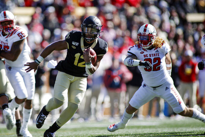 Wake Forest quarterback Jamie Newman (12) runs for a touchdown against North Carolina State in the first half an NCAA college football game in Winston-Salem, N.C., Saturday, Nov. 2, 2019. (AP Photo/Nell Redmond)