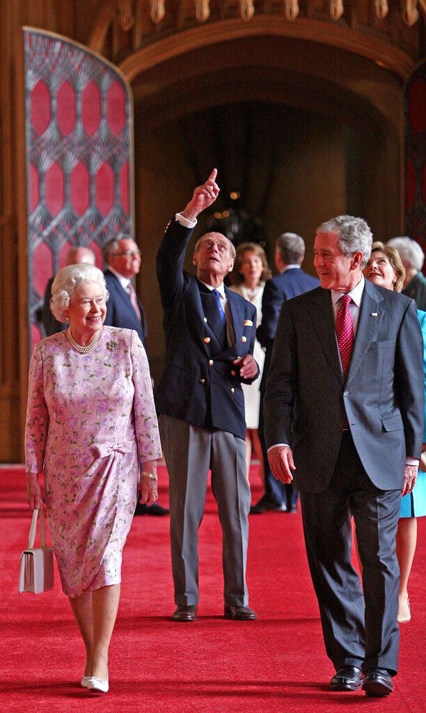 FILE - In this June 15, 2008 file photo, Queen Elizabeth II and Prince Philip, the Duke of Edinburgh, pointing, walk with U.S. President George Bush and his wife Laura, in St George's Hall, Windsor Castle, in Windsor, England. (Nick Ray, Pool Photo via AP, File)