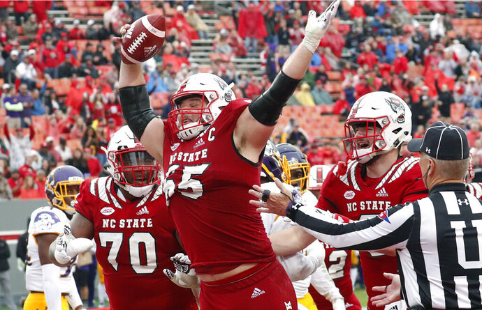 FILE - In this Dec. 1, 2018, file photo, North Carolina State's Garrett Bradbury (65) celebrates after he scored a touchdown during the second half of NCAA college football game, in Raleigh, N.C.Bradbury is a possible pick in the 2019 NFL Draft. (AP Photo/Chris Seward, File)