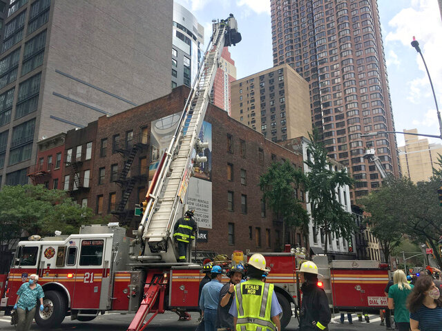 In this image provided by the New York Fire Department (FDNY), firefighters work the scene after the brick facade of a vacant parking garage in Manhattan partially collapsed on Wednesday, July 8, 2020, in New York. One person suffered minor injuries from falling bricks and was treated by emergency services workers. (FDNY via AP)
