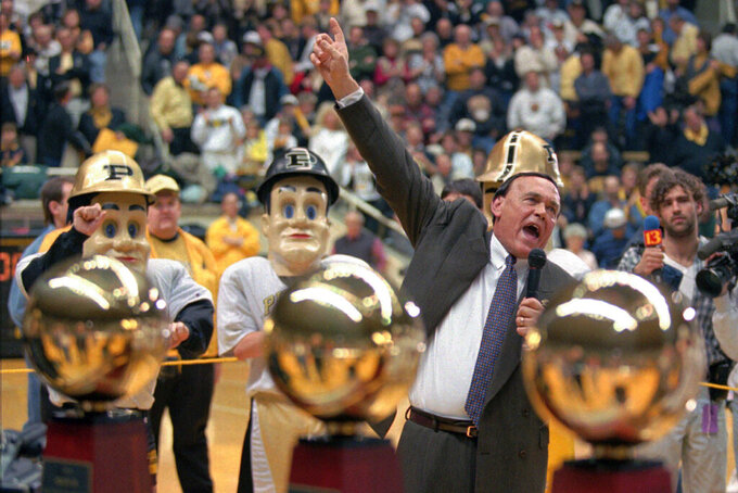 FILE - Purdue coach Gene Keady, framed by the three Big Ten Championship trophies, reacts to the crowd after capturing his third-straight Big Ten Championship by defeating Northwestern 79-56 in West Lafayette, Ind., in this Saturday, March 2, 1996, file photo. Tony Hinkle turned Butler's pass-and-cut offense of the 1920s into a coaching textbook for generations. Bob Knight and Gene Keady added their own revisions following Hinkle's forced retirement in 1970. Today, those three remain the gold standard of basketball innovation in Indiana, a state where successful coaches have spent more than a century testing novel concepts, breaking barriers and polishing philosophies before introducing them America. (AP Photo/Michael Conroy, File)