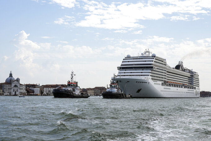 FILE - In this June 5, 2021 file photo, the MSC Orchestra cruise ship leaves Venice, Italy. UNESCO's World Heritage Committee is debating Thursday, July 22, 2021, whether Venice and its lagoon environment will be designated a world heritage site in danger due to the impact of over-tourism alongside the steady decline in population and poor governance. (AP Photo/Antonio Calanni, file)