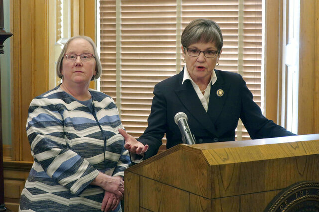 Kansas Gov. Laura Kelly, right, answers questions from reporters about her plans to merge social services agencies as Laura Howard, left, her top social services administrator, watches during a news conference, Wednesday, Jan. 8, 2020, at the Statehouse in Topeka, Kansas. Kelly says merging the two agencies into a single Department of Human Services will improve the delivery of services. (AP Photo/John Hanna)