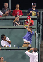 Fans duck for cover from the incoming ball on a two run home run by Philadelphia Phillies' Bryce Harper in the fifth inning during a baseball game against the Boston Red Sox at Fenway Park in Boston, Wednesday, Aug. 21, 2019. (AP Photo/Charles Krupa)