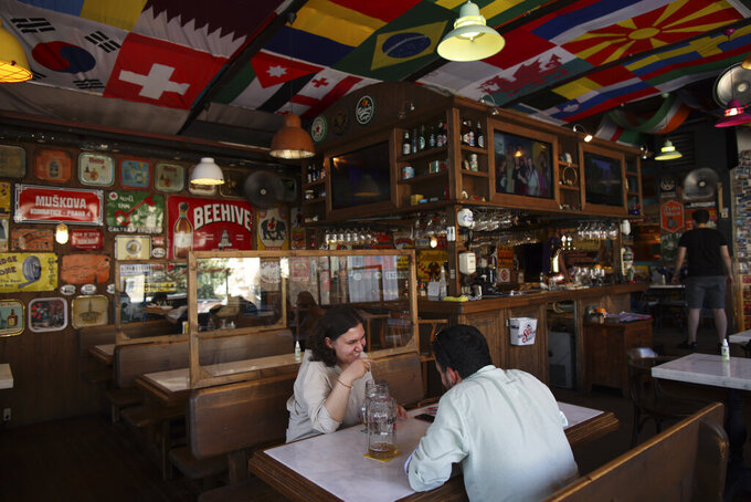 People sit in a restaurant in Istanbul, Thursday, July 1, 2021. Turkey's government  on Thursday eased restrictions in place to curb the spread of the coronavirus, and have reopened theaters, cinemas and other entertainment centers.  (AP Photo/Emrah Gurel)