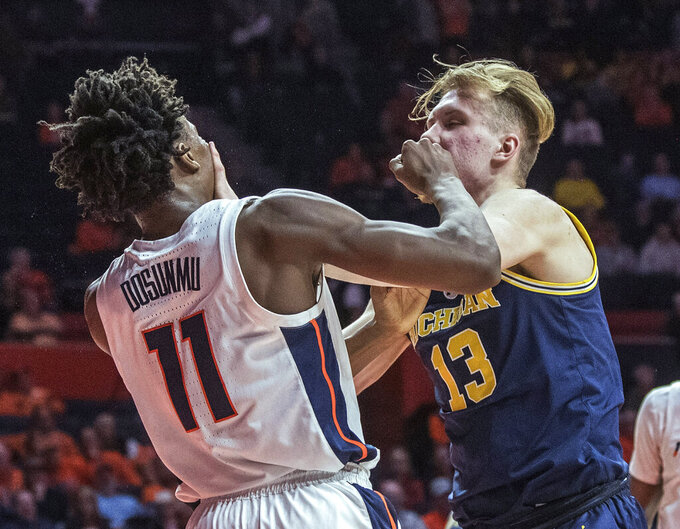Illinois guard Ayo Dosunmu (11) and Michigan forward Ignas Brazdeikis (13) tangle after a foul during the second half of an NCAA college basketball game in Champaign, Ill., Thursday, Jan. 10, 2019. Both players were called for a technical foul. Michigan won 79-69. (AP Photo/Rick Danzl)