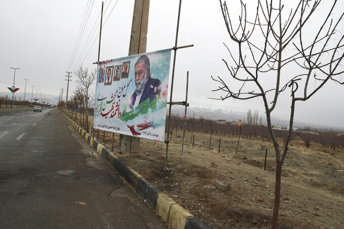 """A billboard carries a portrait of Mohsen Fakhrizadeh, an Iranian scientist linked to the country's nuclear program who was killed by unknown assailants last month, at the site of his killing in Absard east of the capital, Tehran, Iran, Wednesday, Dec. 16, 2020. Iran's supreme leader and the country's president both warned America on Wednesday that the departure of President Donald Trump does not immediately mean better relations between the two nations. The billboard also shows other slain nuclear scientists. The Persian reads: """"the site of ascension of martyred scientist Mohsen Fakhrizadeh to heaven."""" (AP Photo/Vahid Salemi)"""