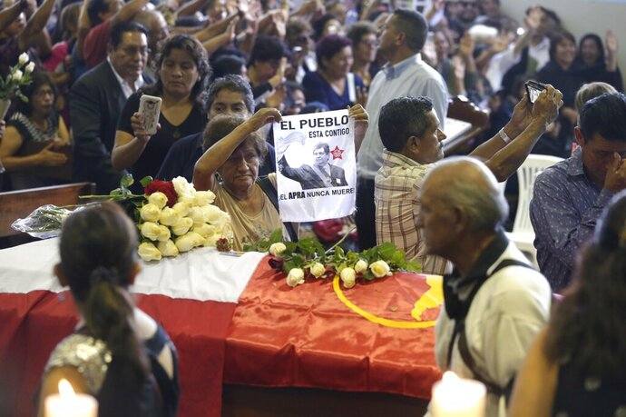 A woman holds up an image of Peru's late President Alan Garcia next to his coffin on the second day of his wake at his party's headquarters in Lima, Peru, Thursday, April 18, 2019. Garcia shot himself in the head and died Wednesday as officers waited to arrest him in a massive graft probe that has put the country's most prominent politicians behind bars and provoked a reckoning over corruption. (AP Photo/Martin Mejia)