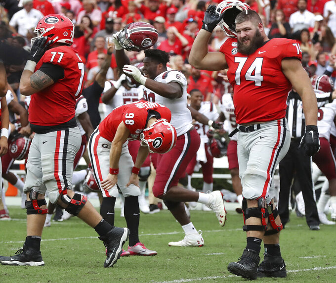 Georgia kicker Rodrigo Blankenship (98) bends over dejected reacting to missing a field goal attempt in double over time as South Carolina celebrates a 20-17 upset victory  in an NCAA college football game, Saturday, Oct., 12, 2019, in Athens, Ga. (Curtis Compton/Atlanta Journal-Constitution via AP)