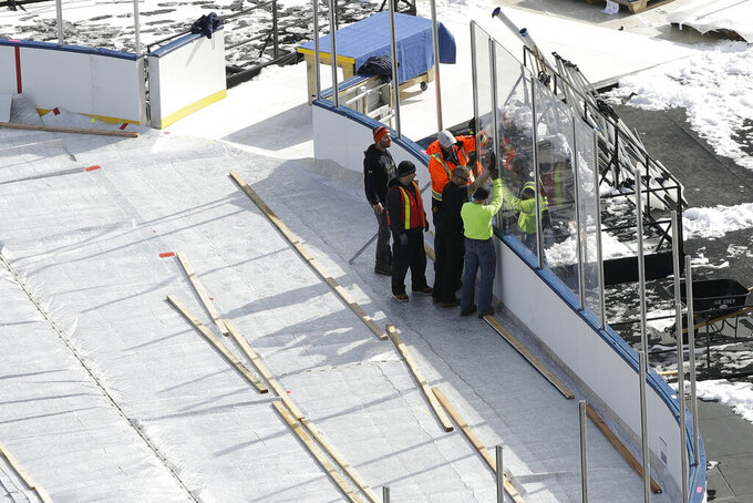 Workers instal the protective glass as they stand upon the ice covered by an insulated tarp ahead of the NHL Winter Classic hockey game between the Pittsburgh Penguins and Philadelphia Flyers, in Philadelphia, Thursday, Feb. 21, 2019. When the Flyers host the Penguins on Saturday at Lincoln Financial Field, it'll be the 27th NHL outdoor game since 2003, and next season's Winter Classic is at the Cotton Bowl in Dallas. There's no fear of the variable climate in Texas in early January and almost no limit to where these games can go. (AP Photo/Matt Rourke)