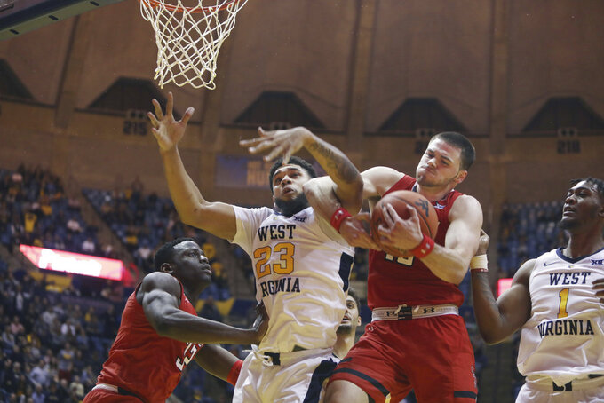 West Virginia forward Esa Ahmad (23) and Texas Tech guard Matt Mooney (13) battle for a rebound during the second half of an NCAA college basketball game Wednesday, Jan. 2, 2019, in Morgantown, W.Va. Texas Tech defeated West Virginia 62-59. (AP Photo/Raymond Thompson)