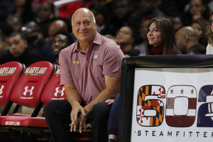 Hall of Fame Baltimore Orioles shortstop Cal Ripken Jr., left, sits with his wife Laura S. Kiessling, Anne Arundel County, Md., circuit court judge, during the second half of an NCAA college basketball game between Maryland and Rhode Island, Saturday, Nov. 9, 2019, in College Park, Md. (AP Photo/Julio Cortez)