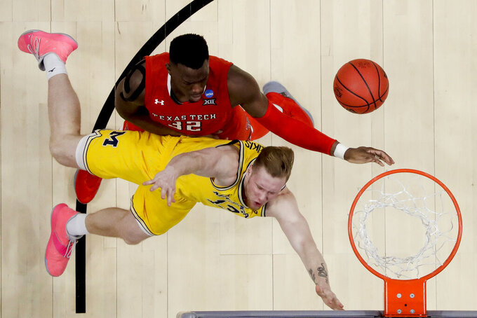 Texas Tech center Norense Odiase, top, fouls Michigan center Jon Teske during the second half an NCAA men's college basketball tournament West Region semifinal Thursday, March 28, 2019, in Anaheim, Calif. (AP Photo/Marcio Jose Sanchez)