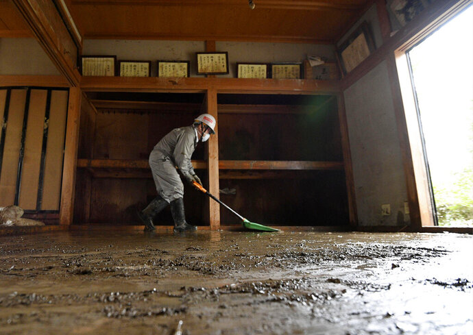 A volunteer continues to clean up mud from last week's Typhoon Hagibis, in Nagano, central Japan, Monday, Oct. 21, 2019. Japan is bracing for two more storms heading its way a week after a typhoon devastated the country's central and northern regions. (Keisuke Koito/Kyodo News via AP)