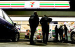 FILE - In this Jan. 10, 2018, file photo, U.S. Immigration and Customs Enforcement agents serve an employment audit notice at a 7-Eleven convenience store in Los Angeles. More local governments in California are resisting the state's efforts to resist the Trump administration's immigration crackdown, and political experts see politics at play as Republicans try to fire up voters in a state where the GOP has grown weak. Leaders in the Orange County city of Los Alamitos are scheduled to vote Monday, April 15, on a proposal for a local law to exempt the community from the state law. (AP Photo/Chris Carlson, File)