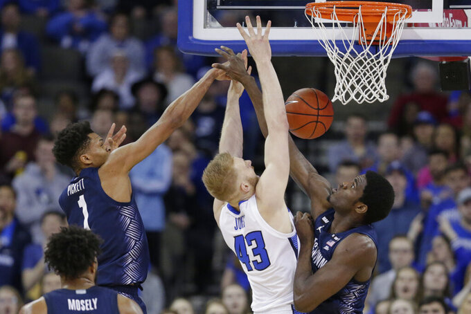 Georgetown's Timothy Ighoefe, right, knocks the ball away from Creighton's Kelvin Jones (43) with Jamorko Pickett (1), during the first half of an NCAA college basketball game in Omaha, Neb., Wednesday, March 4, 2020. (AP Photo/Nati Harnik)