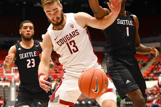 Washington State forward Jeff Pollard (13) fends off Seattle forward Myles Carter (1) for the ball on the baseline as Seattle guard Terrell Brown (23) looks in the first half of an NCAA college basketball game, Thursday, Nov. 7, 2019, in Pullman, Wash. (Pete Caster/The Lewiston Tribune via AP)
