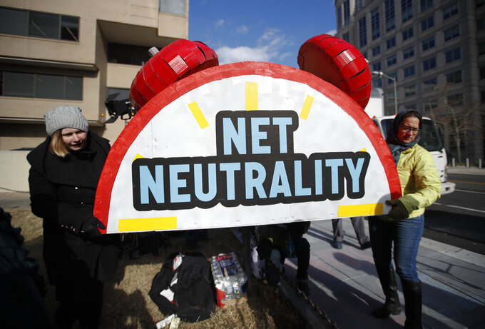 """FILE - In this Dec. 14, 2017, file photo, Sammi LeMaster, left, and Katherine Fuchs, right, carry the top of an alarm clock display that reads """"Net Neutrality"""" after a protest at the Federal Communications Commission in Washington, where the FCC was scheduled to meet and vote on net neutrality. More than three years ago, Trump-era regulators killed federal net neutrality regulations designed to prevent major internet providers from exploiting their dominance to favor certain services or apps over others. In response, seven states and Puerto Rico enacted their own net neutrality policies. The most expansive effort of this sort was in California, which will start enforcing its law on Thursday, March 25. (AP Photo/Carolyn Kaster, File)"""