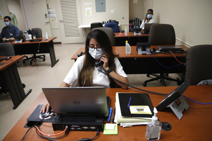 FILE - In this Wednesday, May 13, 2020, file photo, Maria Fernanda works on contact tracing at the Florida Department of Health in Miami-Dade County, during the coronavirus pandemic, in Doral, Fla. In state after state, local health departments charged with doing the detective work of running down the contacts of coronavirus patients are falling well short of the number of people needed to do the job. (AP Photo/Lynne Sladky)