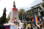 Activists protest Spanish colonization at the Christopher Columbus monument which they painted red to symbolize blood in La Paz, Bolivia, Monday, Oct. 12, 2020, as they mark Decolonization Day, also known as Day of the Race. (AP Photo/Juan Karita)