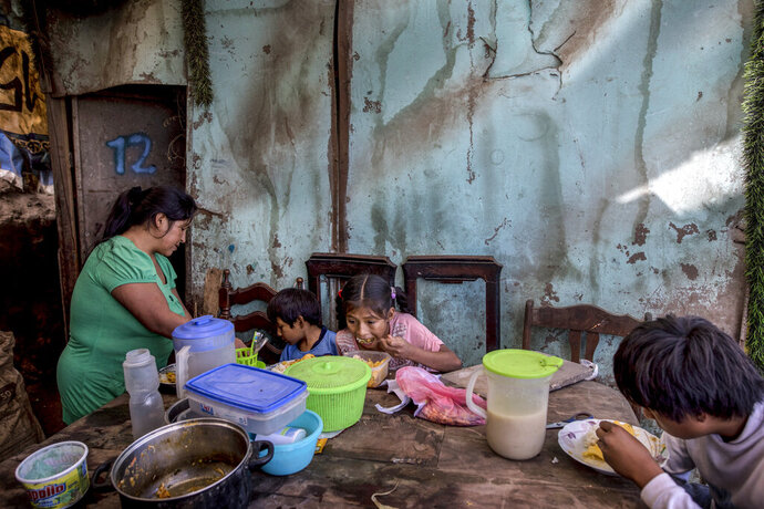 Consuelo Pascacio's three children; Estiben 4, Estefany, 11, and Javier, 14, dig into a chicken rice stew she picked up at a