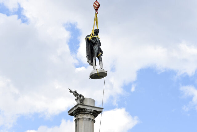 The statue of former U.S. vice president and slavery advocate John C. Calhoun hovers above its monument after contractors completed a 17-hour removal process on Wednesday, June 24, 2020, in Charleston, S.C. (AP Photo/Meg Kinnard)