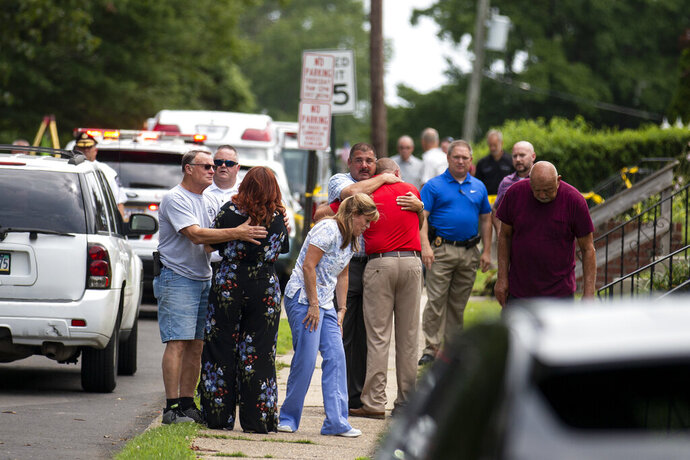 Community members and family console one another near the intersection of Beech and Rively Ave in Alden, Pa., after two workers were found dead in a sewer manhole in Alden, Delaware County, Pa., on Thursday, July 11, 2019. (Tyger Williams/Philadelphia Inquirer via AP)