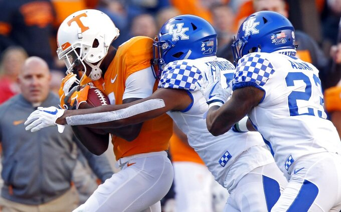 Tennessee tight end Dominick Wood-Anderson (4) catches a pass as he's tackled by Kentucky safety Mike Edwards (7) and safety Tyrell Ajian (23) in the first half of an NCAA college football game Saturday, Nov. 10, 2018, in Knoxville, Tenn. (AP Photo/Wade Payne)