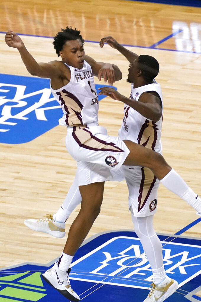 Florida State guard Scottie Barnes, left, and teammate Florida State guard Sardaar Calhoun (24) celebrate their 69-66 win over North Carolina of an NCAA college basketball game in the semifinal round of the Atlantic Coast Conference tournament in Greensboro, N.C., Friday, March 12, 2021. (AP Photo/Gerry Broome)