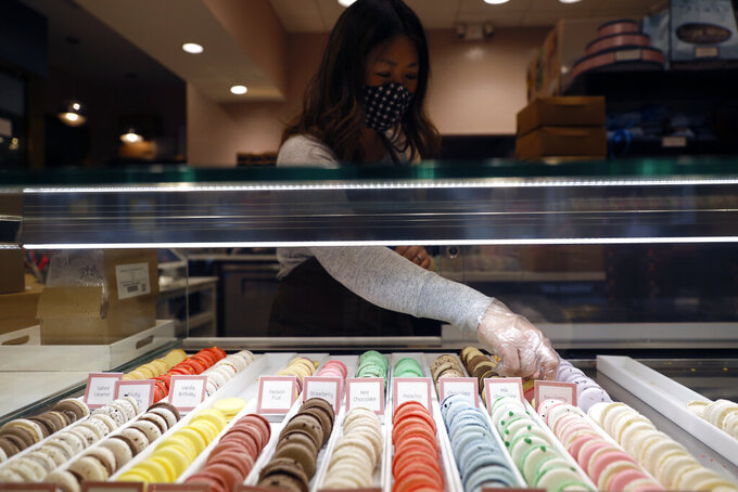 Sugar Bliss Bakery owner Teresa Ging organizes arranges bakery items in her shop in Chicago's famed Loop, Tuesday, May 4, 2021. In many downtown areas where companies closed their offices and commuting ground to a halt, sandwich shops, bakeries and other small businesses are waiting with guarded optimism for their customers to return. (AP Photo/Shafkat Anowar)