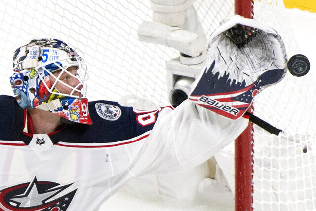 Columbus Blue Jackets goaltender Elvis Merzlikins makes a save during second-period NHL hockey game action against the Montreal Canadiens in Montreal, Sunday, Feb. 2, 2020. (Graham Hughes/The Canadian Press via AP)