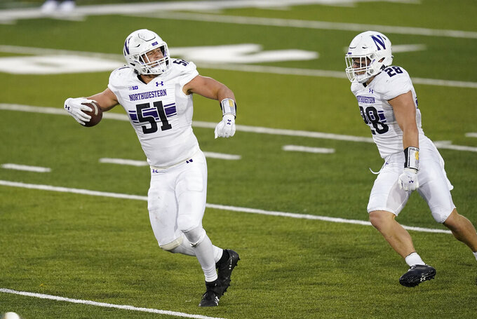 Northwestern linebacker Blake Gallagher (51) celebrates with teammate Chris Bergin, right, after intercepting a pass during the second half of an NCAA college football game against Iowa, Saturday, Oct. 31, 2020, in Iowa City, Iowa. (AP Photo/Charlie Neibergall)