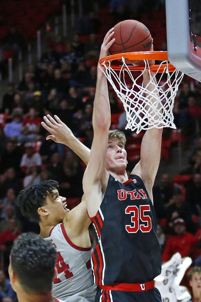 Utah center Branden Carlson (35) dunks next to Stanford forward Spencer Jones (14) in overtime of an NCAA college basketball game Thursday, Feb. 6, 2020, in Salt Lake City. (AP Photo/Rick Bowmer)