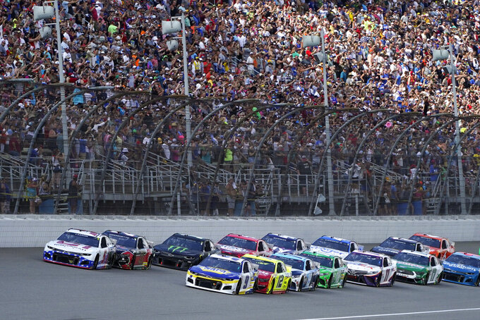 Kyle Larson, front left, leads the field to start the NASCAR Cup Series auto race at Michigan International Speedway, Sunday, Aug. 22, 2021, in Brooklyn, Mich. (AP Photo/Carlos Osorio)