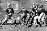 "FILE - In this Sept. 13, 1942, file photo, Washington Redskins quarterback Sammy Baugh, left, drops back to pass against the Chicago Bears during a football game in Washington. ""Slingin'"" Sammy Baugh, Washington's top draft choice in 1937, gets credit for being the NFL's first big-yardage passer. (AP Photo/File)"