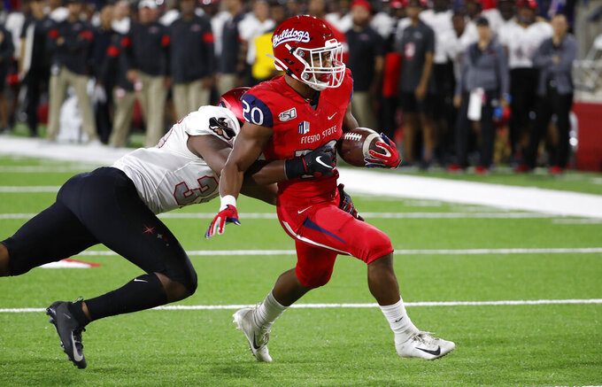 UNLV linebacker Jacoby Windmon tries to tackle Fresno State running back Ronnie Rivers, who scores a touchdown during the first half of an NCAA college football game in Fresno, Calif., Friday, Oct. 18, 2019. (AP Photo/Gary Kazanjian)