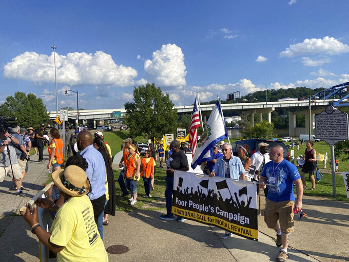 Demonstrators outraged with Sen. Joe Manchin's opposition to a sweeping overhaul of U.S. election law, march, Monday, June 14, 2021, in Charleston, W.Va. (AP Photo/Cuneyt Dil)