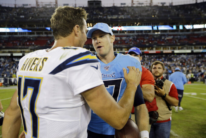 Los Angeles Chargers quarterback Philip Rivers, left, meets with Tennessee Titans quarterback Ryan Tannehill after an NFL football game Sunday, Oct. 20, 2019, in Nashville, Tenn. The Titans won 23-20. (AP Photo/James Kenney)